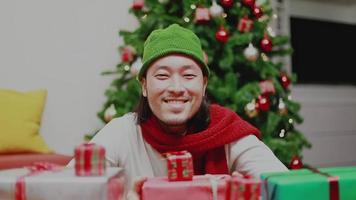 Asian man smiling looking at the camera having a Christmas tree celebrates the new year at home. video