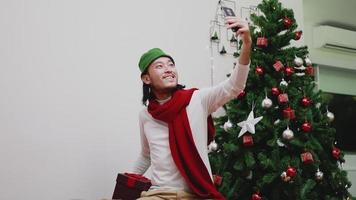 Asian man using a smartphone video chat presents a gift box with friends.
