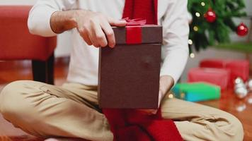 Asian men open the gift box in the living room at home having a Christmas tree in the background. video