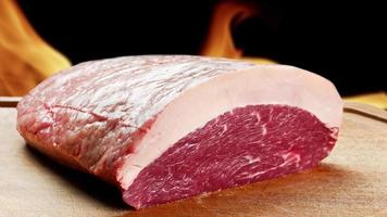 Picanha, traditional Brazilian barbecue with fire background. Raw meat video