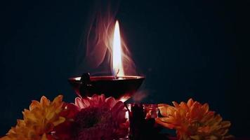 feliz diwali. Quema de lámparas de aceite diya y flores sobre fondo oscuro video