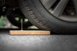 Close up a metal nail on board wood nearly to puncture into wheel tire photo
