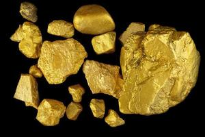 Group of precious gold nugget at black background photo