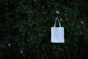 Blank white fabric cloth bag tote at green bush trees foliage Background, Environmental conservation recycling concept photo