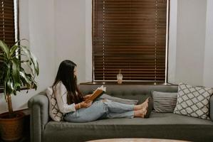 Closeup shot of a South Asian young woman sitting on the sofa and reading a book photo