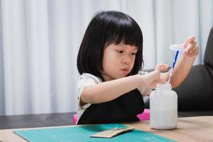 Crafts for kids. Creative child sticking workpiece design with glue. Art and creativity class in school or kindergarten. Preschool kid with fun DIY project. Baby aged 4-5 years old wearing black apron photo