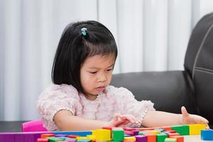 Portrait of a child spending her free time doing activity in house. Kid have fun playing with wooden cube toys. photo