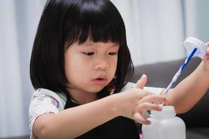 primer plano cara niña aprendiendo artesanía en el aula. Alumno de jardín de infantes tocando pegamento para hacer invención. niño en edad preescolar con divertido proyecto de bricolaje. bebé de 4-5 años con delantal negro. foto