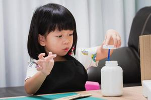 Kindergartener doing crafts shows excited expressions when she opens the glue bottle caps, child wrapped their mouths, having fun making their own creations. Children aged 4-5 years. photo