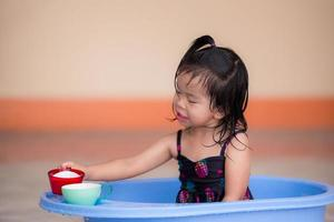 Cute 3 year old girl who sits in blue plastic basin shower. Happy child wet to use a glass to transfer the water. Asian children have a sweet smile. Cool activities. During the summer or spring. photo