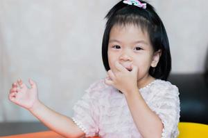A cute little girl is scratching her lips from itching. Children secretly smile. photo