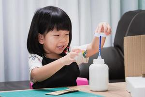 Child are having fun learning through hobbies with arts and crafts, gluing waste paper boxes with glue, imaginative creations, smiling sweet children, kid girl poking their fingers into glue tubes. photo