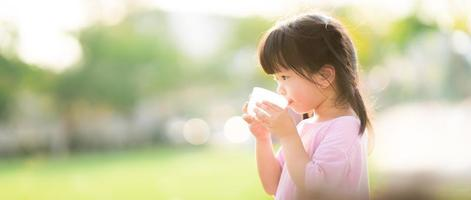 Concept of water are great for kid. Child are drinking from plastic glasses. Natural background. During the summer or spring. The side of a 4 year old girl. photo