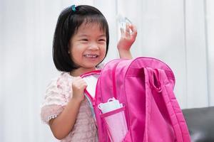 una linda chica se divierte empacando sus maletas para la escuela. chica sosteniendo una botella de gel de alcohol. la mascarilla higiénica está al lado de la bolsa. foto