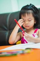 Vertical image. Cute girl is scratching her face due to itching as she sits painting on the table. photo