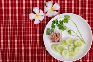 Yum tuna salad is small on a white plate, garnished with melons and fresh green coriander. Red and white plaid fabric background. Vintage style. Decorated with frangipani flowers. photo