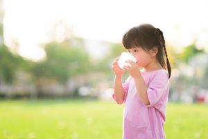 Adorable Asian child girl are drinking fresh water from plastic glasses. Green natural background. In the summer or spring. Side view of kid is 4 year old wearing pink shirt thirsty. photo