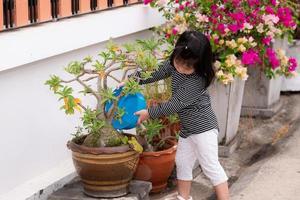 linda chica con una camisa a rayas en blanco y negro está usando un recipiente azul para regar las plantas en una maceta frente a su casa. niño ayudando con las tareas del hogar. niños de 3 a 4 años. foto