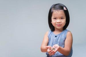 Cute Asian child girl holding coins in her hands. Sweet smiling kid. Happy children playing silver coins. Baby looking at camera. Childhood savings concept. Clean background. Copy space. photo