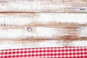 Mantel a cuadros rojo sobre la mesa de madera antigua, concepto de vacaciones foto