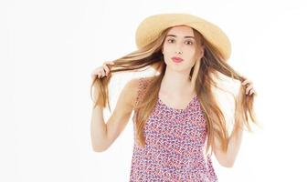 fashion and lifestyle concept - beautiful woman in hat holding her hair curles enjoying summer outdoors isolated on white. photo