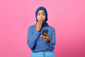 Portrait of shocked young Asian woman holding smartphone and covering mouth with hand photo