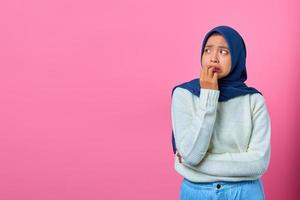 Portrait of young Asian woman looking stressed and nervous with hand on mouth biting nails photo