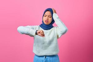 Portrait of young Asian woman worried work deadline stress on pink background photo
