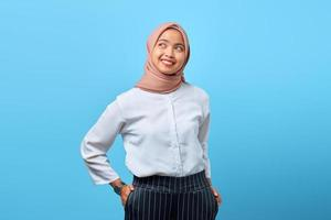 Portrait of charming young Asian woman with good mood over blue background photo