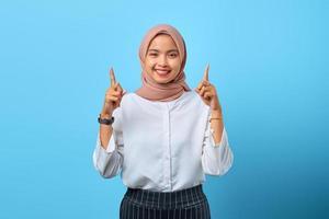 Retrato de joven alegre mujer asiática apuntando hacia la promoción de anuncios directos foto