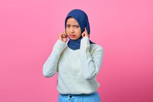 Portrait of angry young Asian woman covering her ears with finger photo
