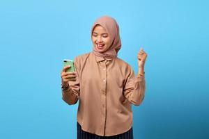 Portrait of excited cheerful young Asian woman celebrating winning with mobile phone on hand photo