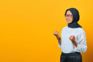 Portrait of excited beautiful Asian woman celebrating success on yellow background photo