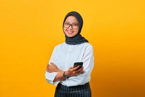 Sonriente joven mujer asiática mediante teléfono móvil y mensajes de texto sobre fondo amarillo foto