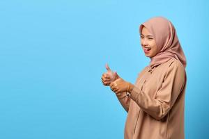 Portrait of excited cheerful young Asian woman showing thumbs up or approval sign to empty space photo