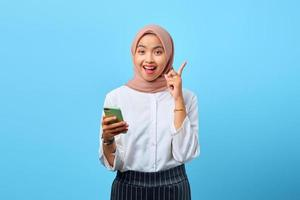Portrait of excited young Asian woman holding mobile phone and raised finger because have solutions photo