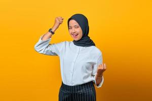 Portrait of excited beautiful Asian woman rejoicing celebrating luck on yellow background photo