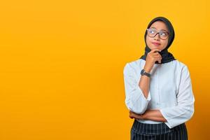 Pensive young Asian woman looks seriously thinking about a question on yellow background photo