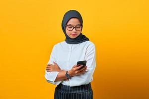 Joven mujer asiática con teléfono móvil y mensaje de texto sobre fondo amarillo foto