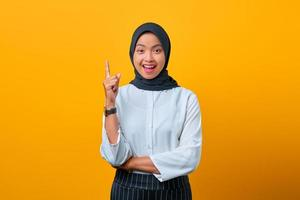 Excited beautiful Asian woman raising index finger and saying idea on yellow background photo