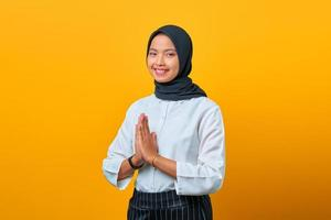 Portrait of smiling young Asian woman welcome expression on yellow background photo