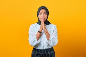 Surprised young Asian woman covering mouth with hands isolated over yellow background photo
