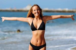 Young blonde woman with beautiful body in swimwear on a tropical beach with open arms. photo