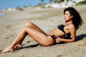 Arabic woman with beautiful body in bikini lying on the beach sand photo