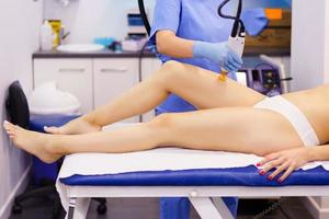 Woman receiving legs laser hair removal at a beauty center. photo