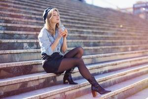 Blonde woman with beret, drinking a natural orange juice in a crystal glass, sitting on some steps. photo