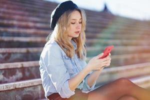 Blonde woman using a smartphone sitting on some city steps, wearing a denim shirt and black beret. photo