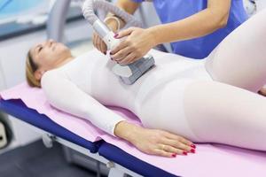 Mujer en traje especial con un masaje de vientre anticelulítico con aparato de spa foto