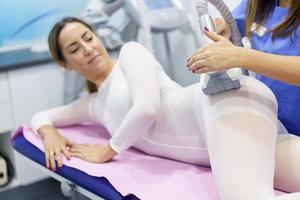 Mujer en traje blanco especial con un masaje anticelulítico con aparato de spa foto