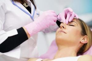 médico que realiza una rinoplastia mediante inyección de ácido hialurónico en la nariz de su paciente. foto